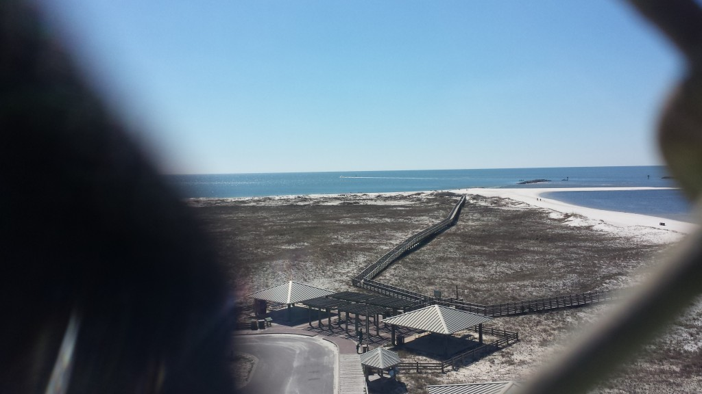 The beach at Gulf Shores Alabama. The dark blurry image on the left is the cyclone fence put up to keep everyone on the bridge.